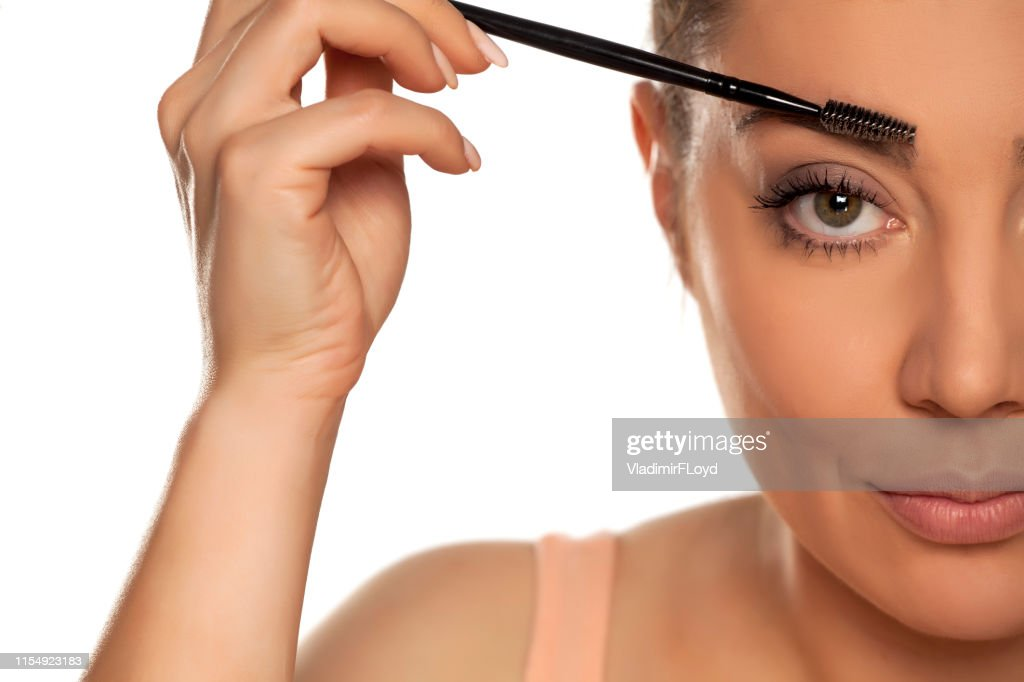 Young woman contouring her eyebrows with dry brush on white background : Stock Photo
