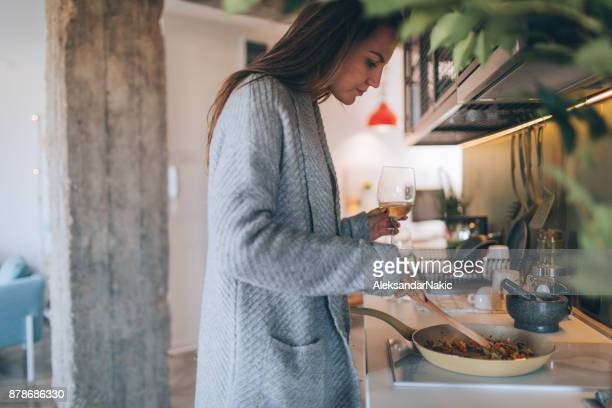 Young woman cooking and drinking wine