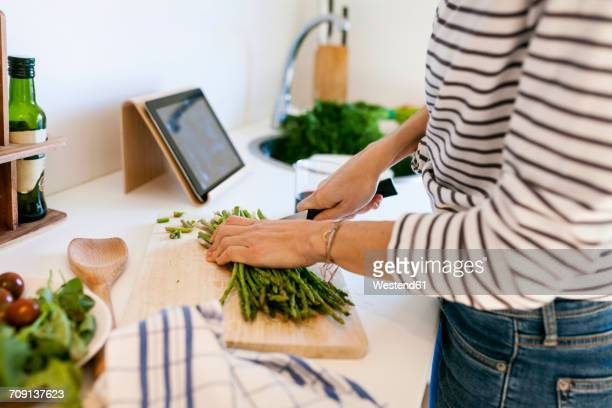 young woman cooking at home using digital tablet for recipe - recipe stock pictures, royalty-free photos & images