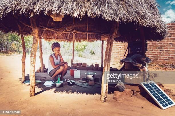 eine junge frau, die maismaze unter einem hut in einem afrikanischen dorf kauern - afrika stock-fotos und bilder