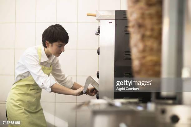 young woman cooking food in fast food shop - sigrid gombert fotografías e imágenes de stock