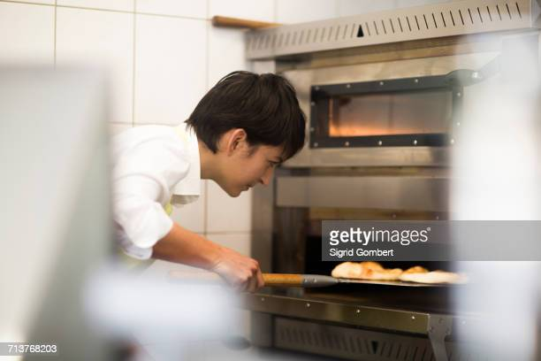 young woman cooking food in fast food shop - sigrid gombert stock pictures, royalty-free photos & images