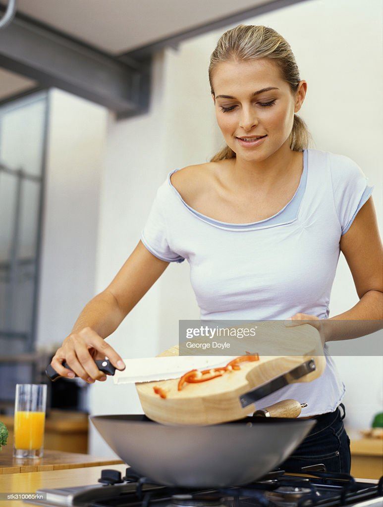 Young Woman Cooking Food In The Kitchen Stock Photo | Getty Images