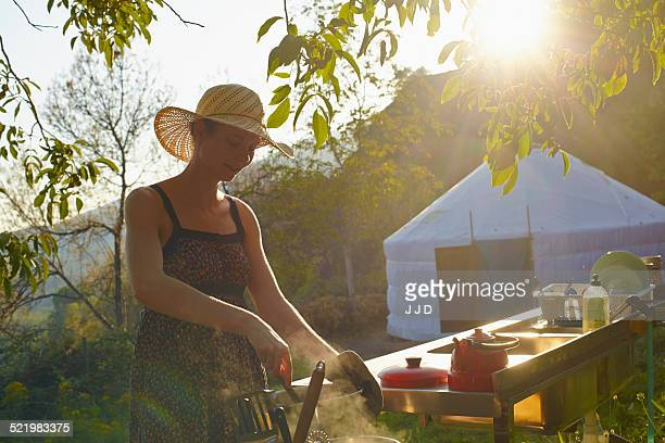 Young woman cooking food whilst glamping, Sierra Nevada, Andalucia Granada, Spain