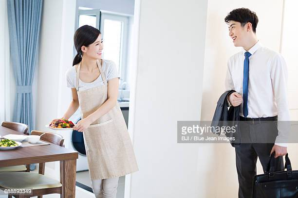 Young woman cooking for husband at home