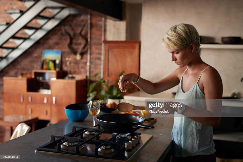 Young woman cooking in loft apartment : Stock Photo