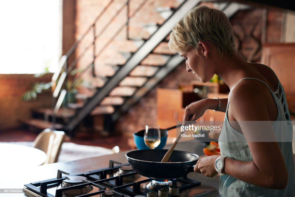 Young woman cooking in loft apartment : Stock-Foto