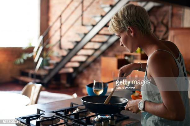 young woman cooking in loft apartment - cooker stock pictures, royalty-free photos & images