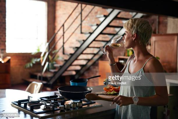 young woman cooking in loft apartment - burner stove top stock pictures, royalty-free photos & images