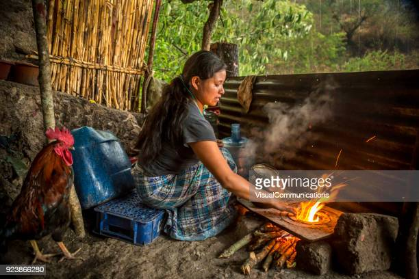 young woman cooking over fire in front of her house. - central america stock pictures, royalty-free photos & images