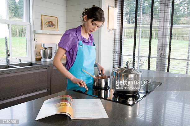 young woman cooking, recipe book - electric stove burner stock pictures, royalty-free photos & images