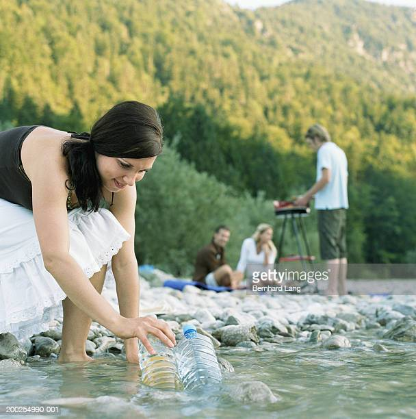 young woman cooling water bottles in river, close-up - bending over in skirt stock pictures, royalty-free photos & images