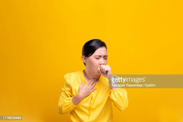 young woman coughing against yellow background - 咳 ストックフォトと画像