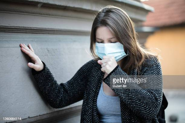young woman coughing under the mask - symptom stock pictures, royalty-free photos & images