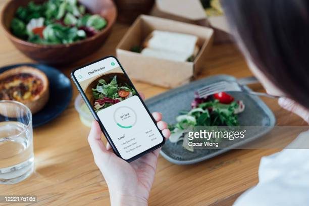 young woman counting calories with smartphone while eating - healthy eating stock pictures, royalty-free photos & images