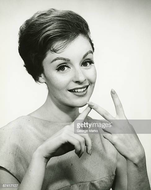 Young woman counting on fingers, posing in studio, (B&W), (Portrait)