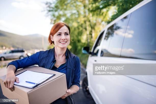 young woman courier by a delivery car, carrying parcels. - carteiro imagens e fotografias de stock
