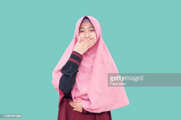 young woman covered her mouth by hand - alleen tieners stockfoto's en -beelden