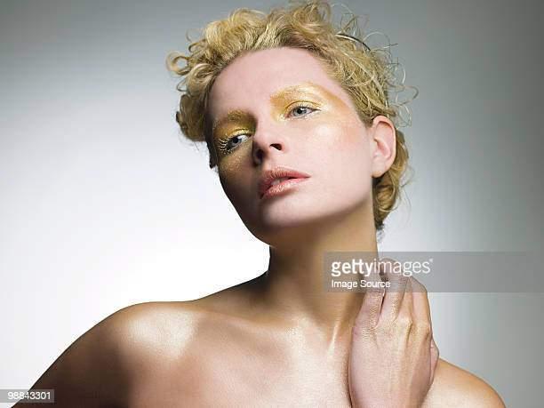 Young woman covered in gold make up
