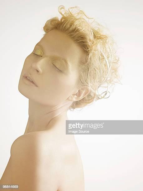 Jeune femme avec maquillage or couvert