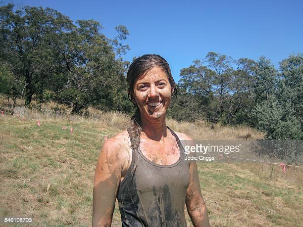 Young woman covered in mud during obstacle course