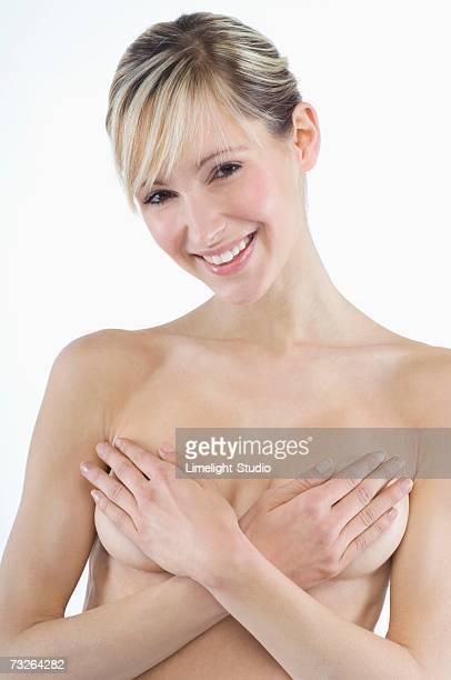 young woman covering breasts, portrait - mani su seno foto e immagini stock