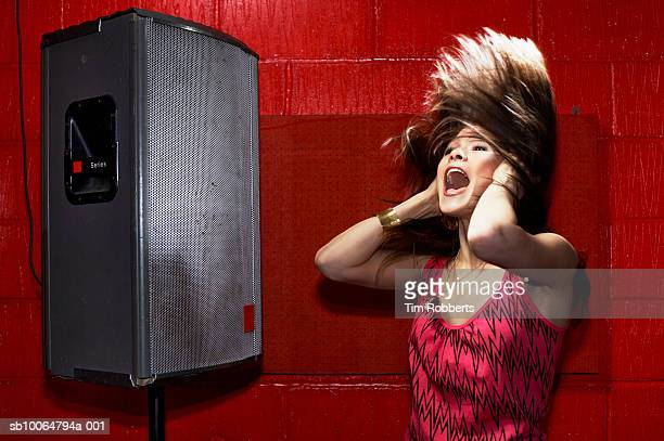 Young woman covering ears and shouting next to loud speaker