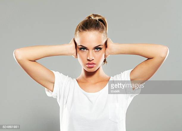 Young woman covering ears with hands