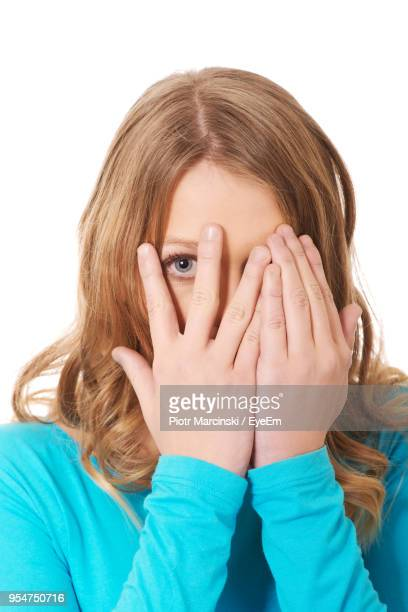 Young Woman Covering Face Against White Background