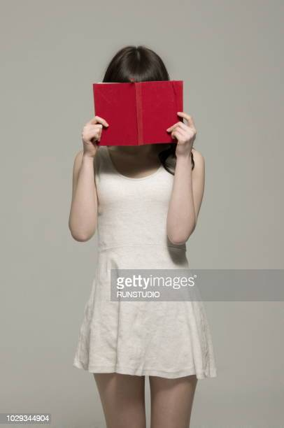 Young woman covering face with book