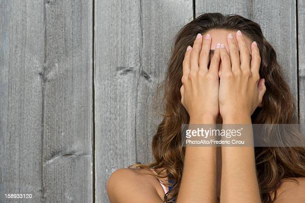 Young woman covering face with hands, portrait