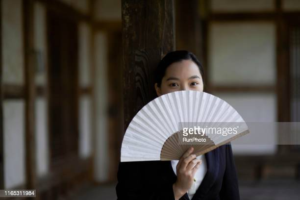young woman covering face with korean traditional fan - korean culture stock pictures, royalty-free photos & images