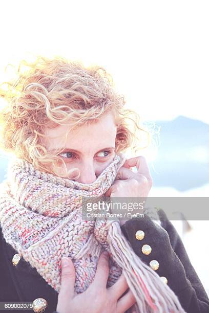 young woman covering face with scarf during winter - bortes stock-fotos und bilder