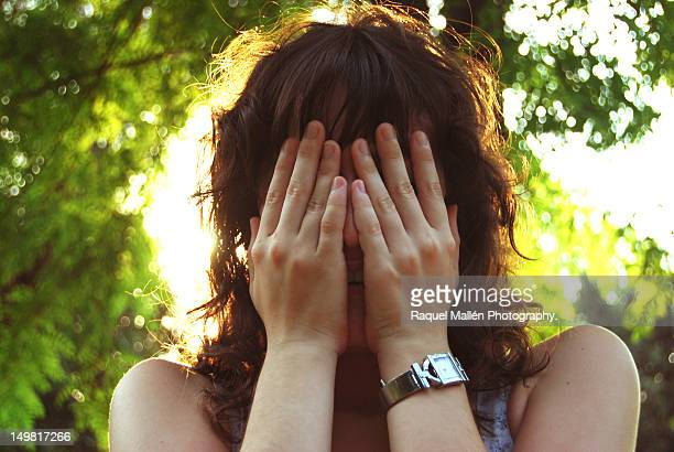 Young woman covering her face with hands