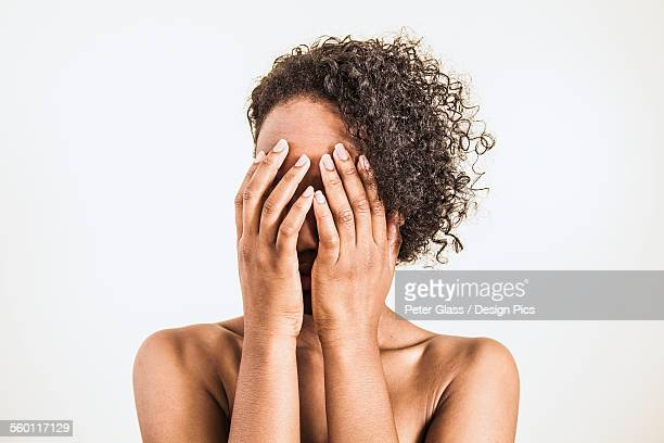 A young woman covering her face with her hands