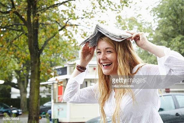 young woman covering her head with a newspaper to protect herself from the rain