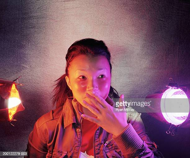 young woman covering her mouth with hand, close-up - gel effect lighting stock photos and pictures