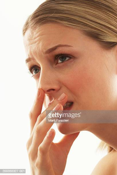 Young woman covering mouth with hand, close-up