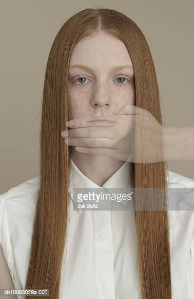 Young woman covering mouth with hand, portrait (digital composite)