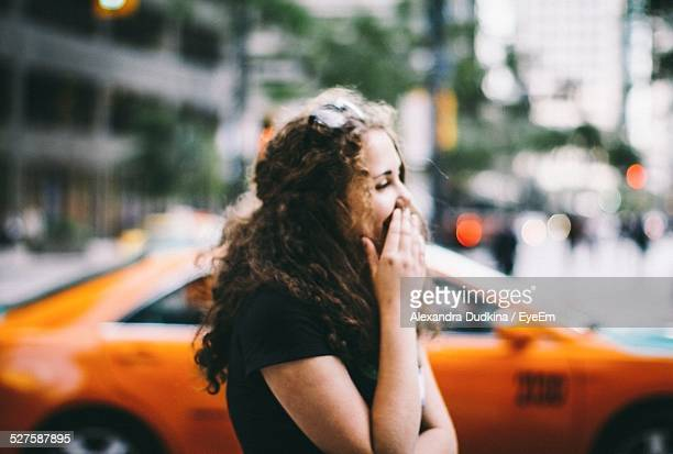 Young Woman Covering Mouth With Hands On City Street