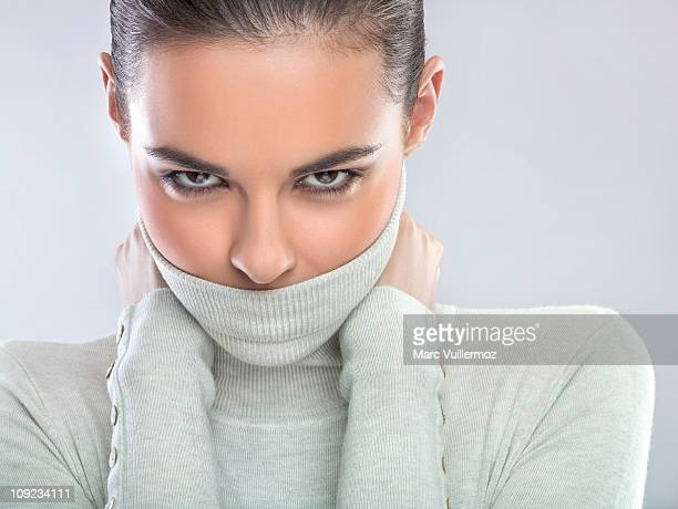Young woman covering mouth with turtleneck