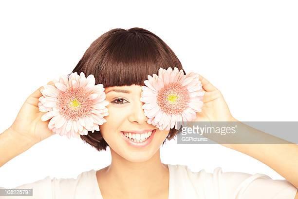 Junge Frau, die ein Auge mit Blüte, auf weißem Hintergrund.