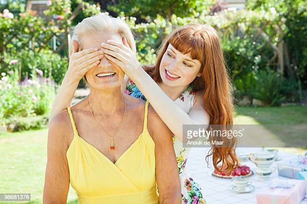 young woman covers eyes of mature woman.