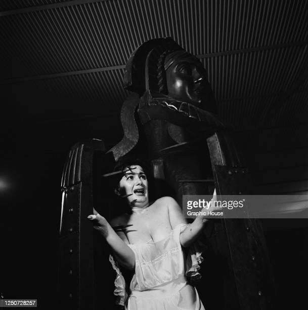 A young woman cowers inside an iron maiden circa 1960