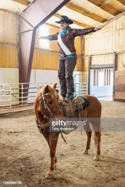 young woman cowgirl standing on her horse - stunt stock pictures, royalty-free photos & images
