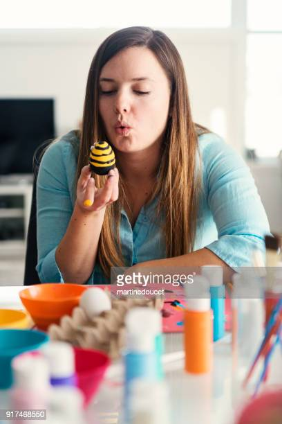 "young woman crafting easter decorations at home. - ""martine doucet"" or martinedoucet stock pictures, royalty-free photos & images"