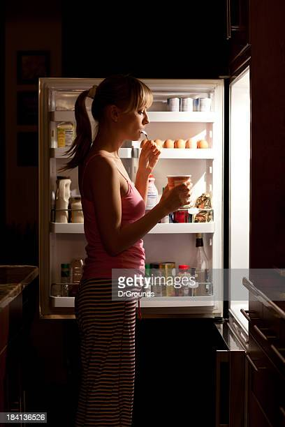 Young woman craving food eating near refrigerator at night