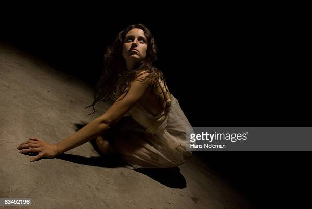 young woman crawling away in fear - female torture stock-fotos und bilder