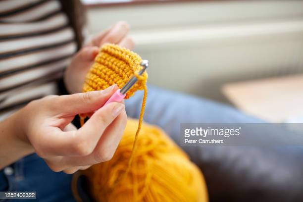 young woman crocheting with yellow wool - crochet stock pictures, royalty-free photos & images