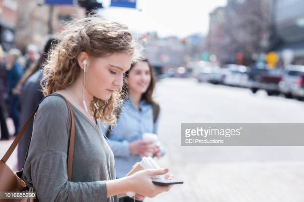 young woman crosses street distracted by digital media - shoulder bag stock pictures, royalty-free photos & images